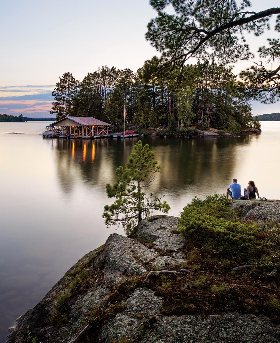 Young couple enjoys calm evening on Northern Minnesota lake