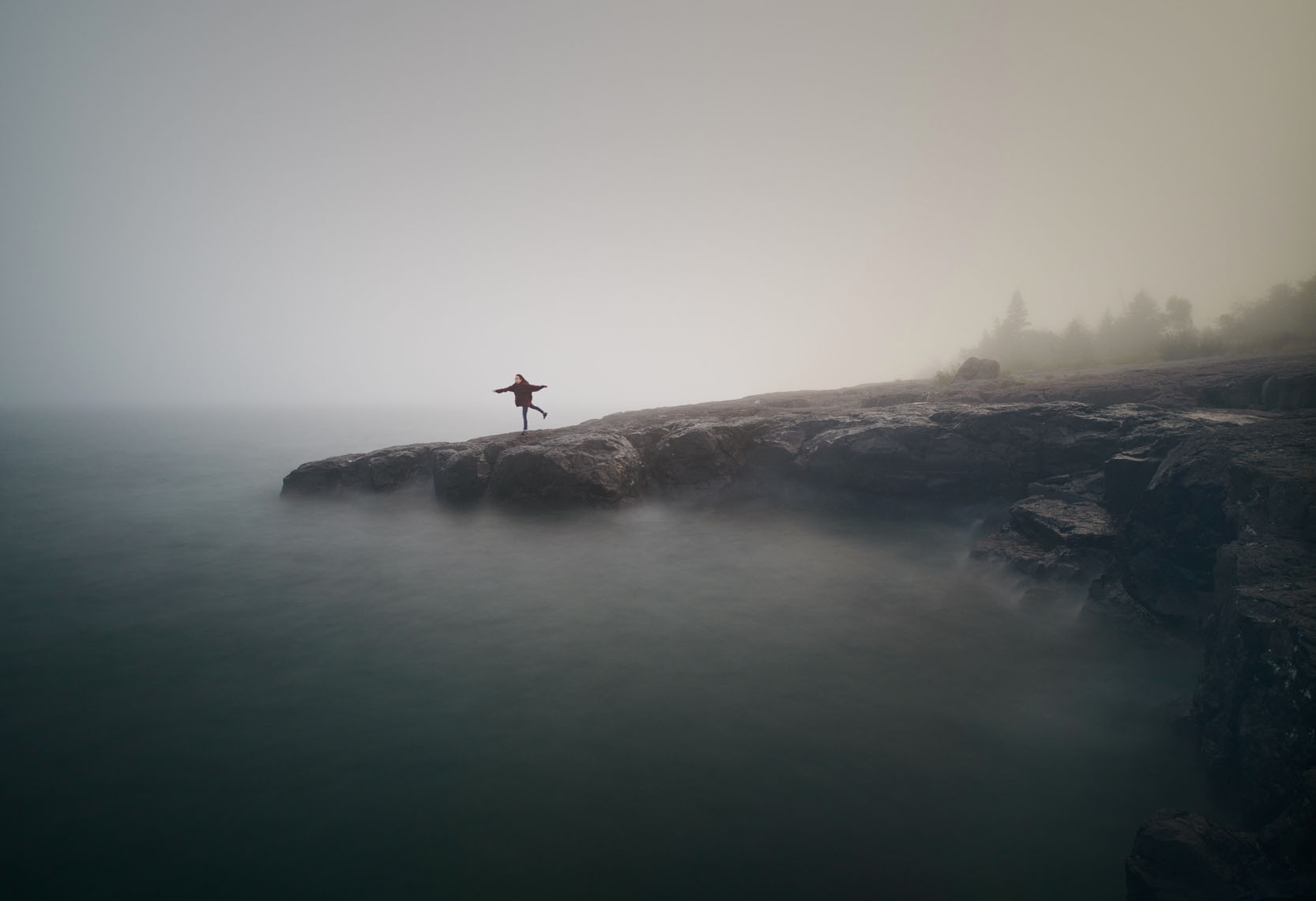Girl practices yoga on ancient Lake Superior volcanic beach