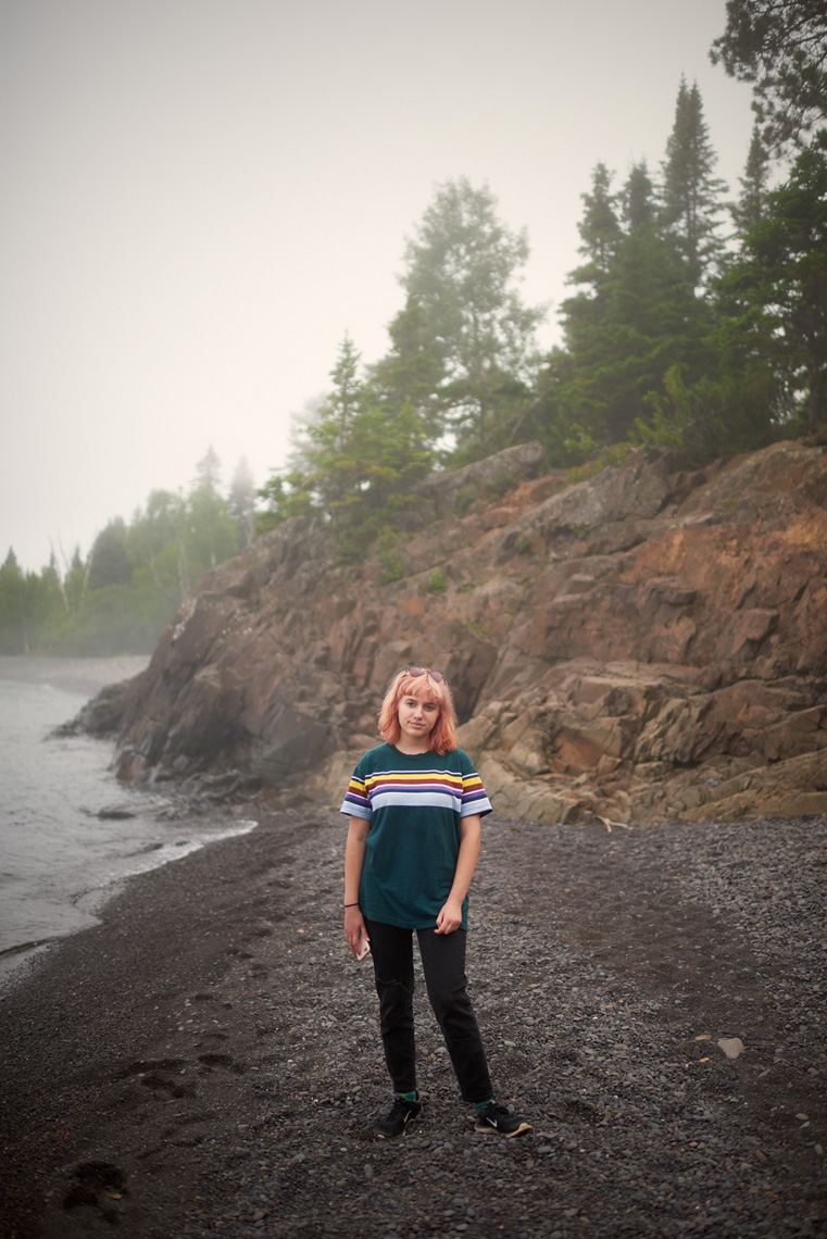 Teenage girl on foggy Lake Superior pebble beach
