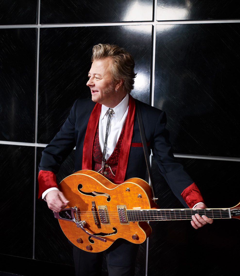 Brian Setzer in suit with guitar for Guitar Aficionado magazine