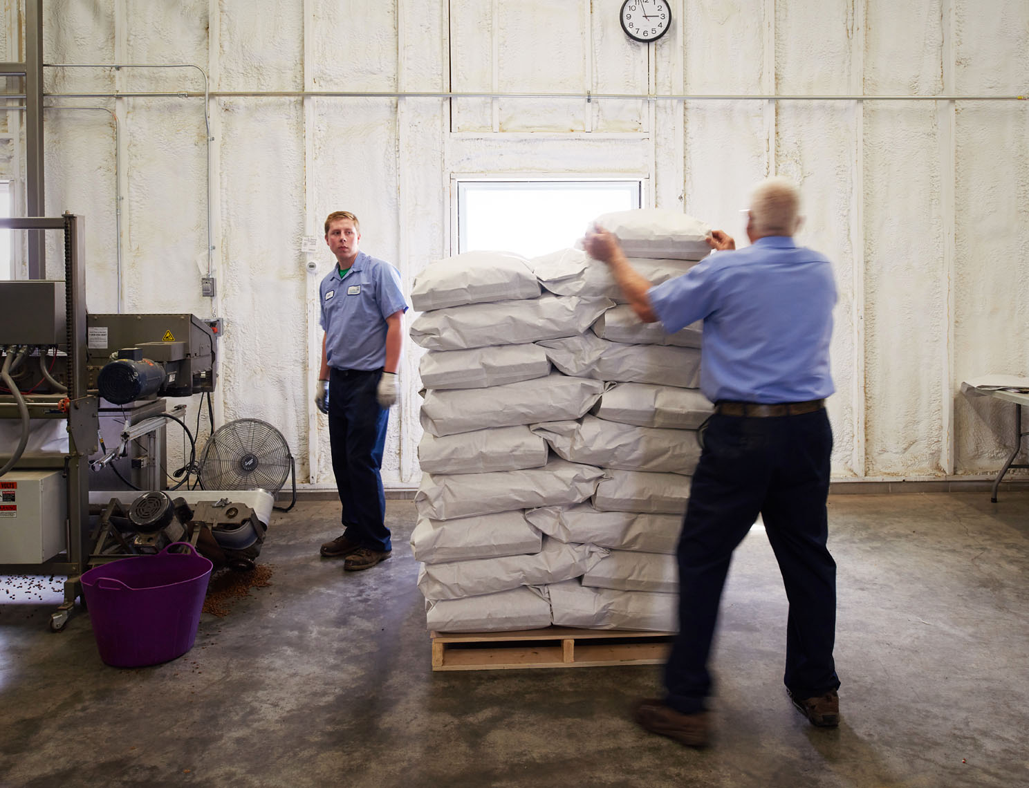 Manufacturing plant workers stack petfood bags portrait