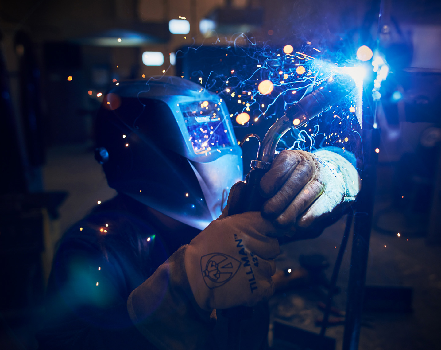 Arc welder with helmet and gloves fabricates metal