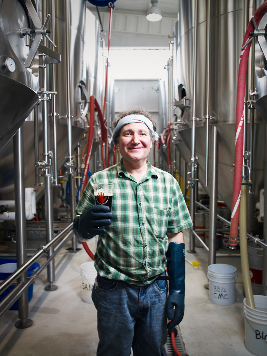 Brewery worker tests beer for flavor portrait industrial