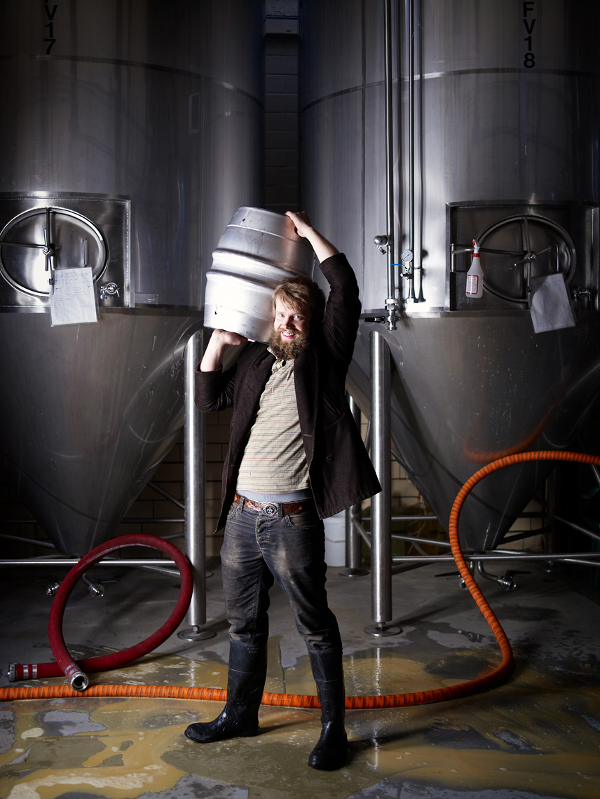 brewery worker lifts keg of beer portrait industrial
