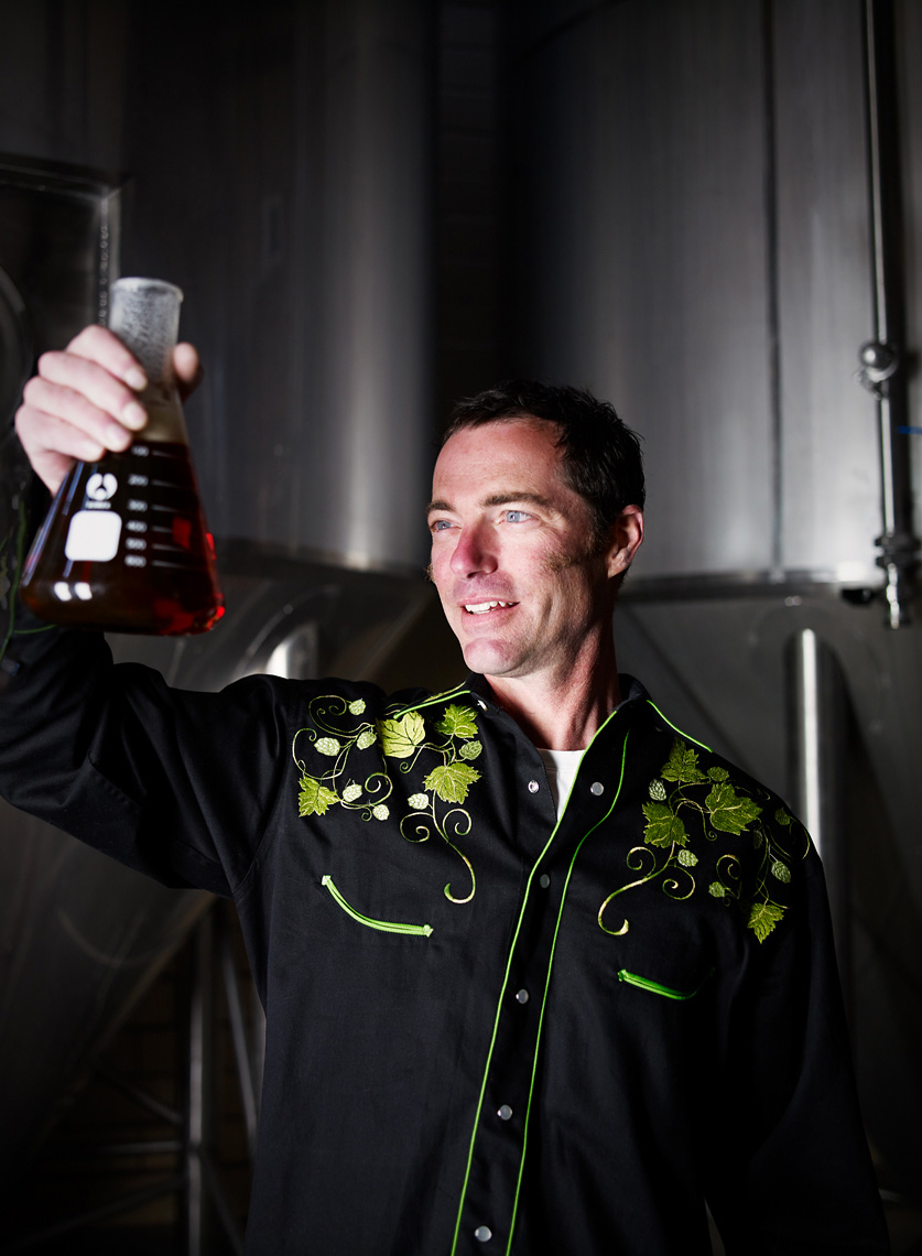 Brewery owner inspects sample beer industrail portrait