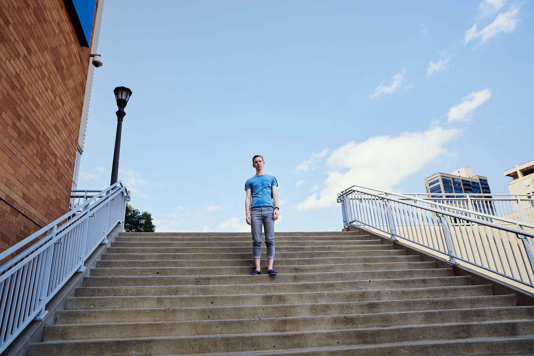 young man on stairs with cloudy sky portrait