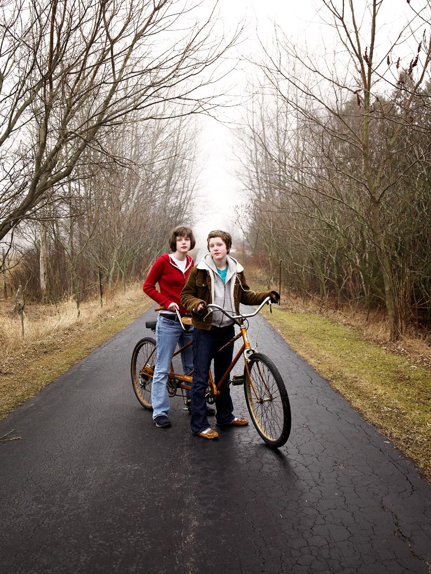 Twins with tandem bicycle on driveway portrait