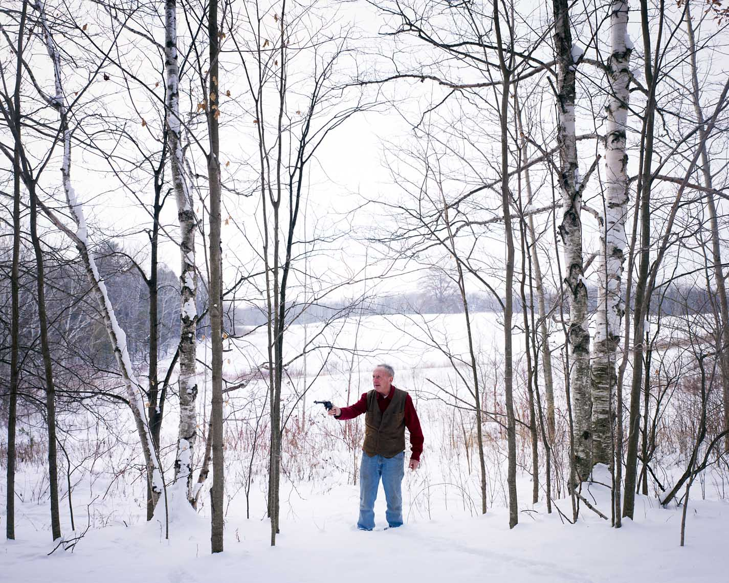 My dad with pistol in snowy wooded field portrait