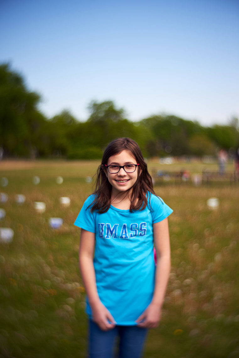 Tween girl wearing glasses in sunny green field portrait