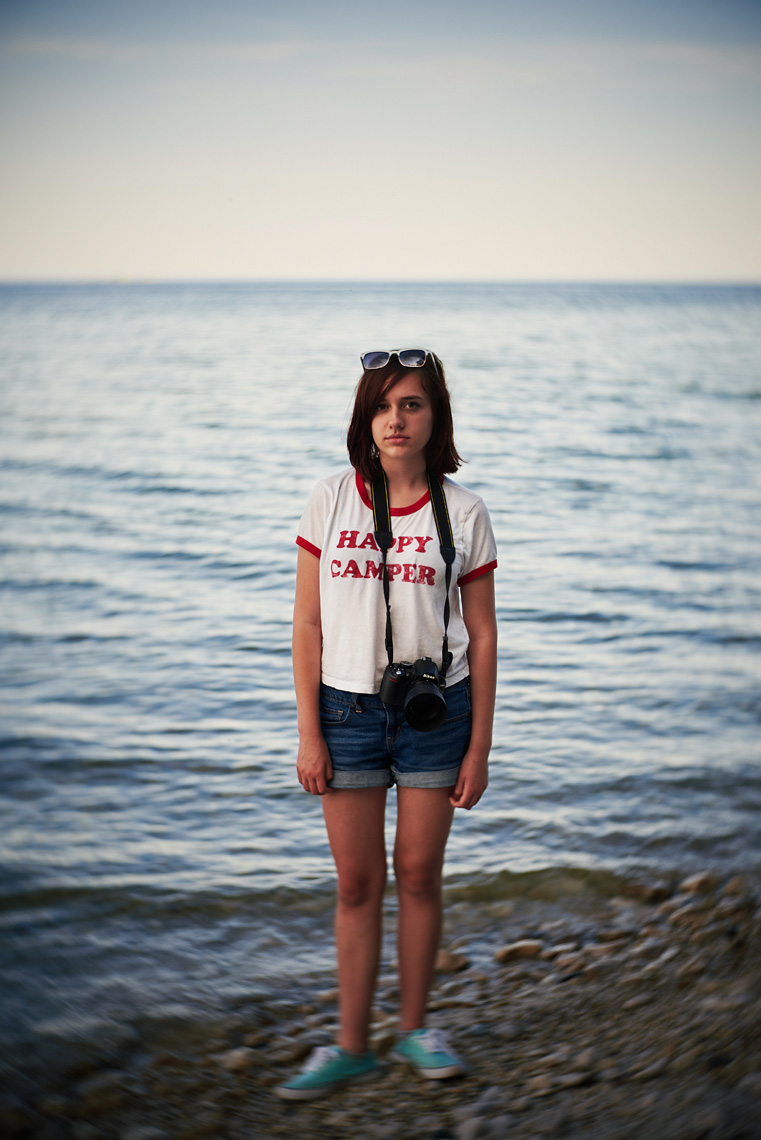 Teen girl with camera on Lake Michigan beach portrait