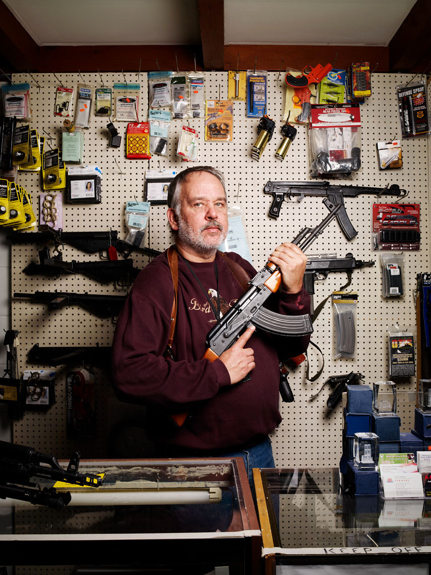 Gun store owner behind counter with Kalishnikov portrait