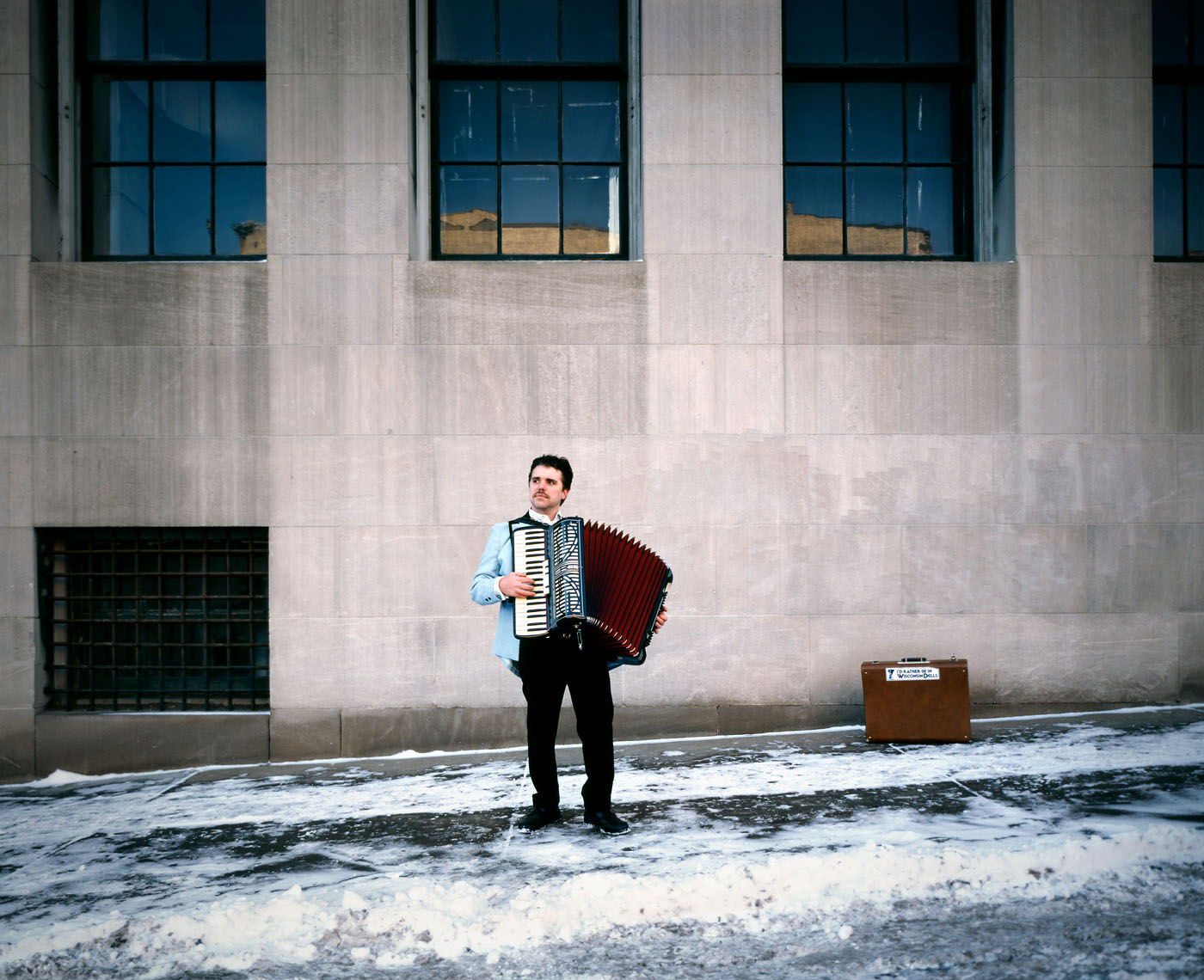 Busker playing accordion in snow portrait
