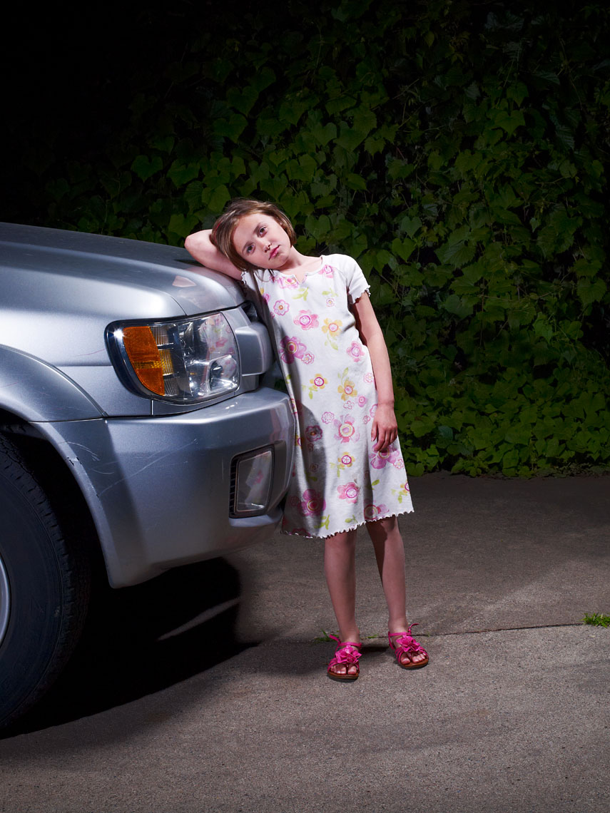 Young girl leans on SUV in driveway portrait