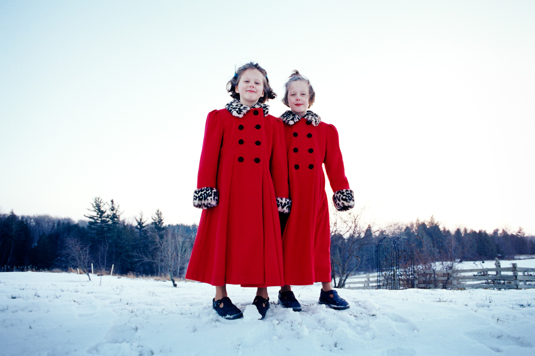 Young twin girls in snow with matching red coats portrait
