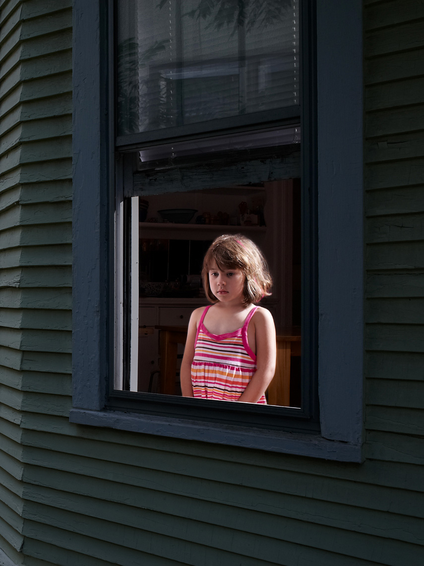 Young girl stares out window portrait