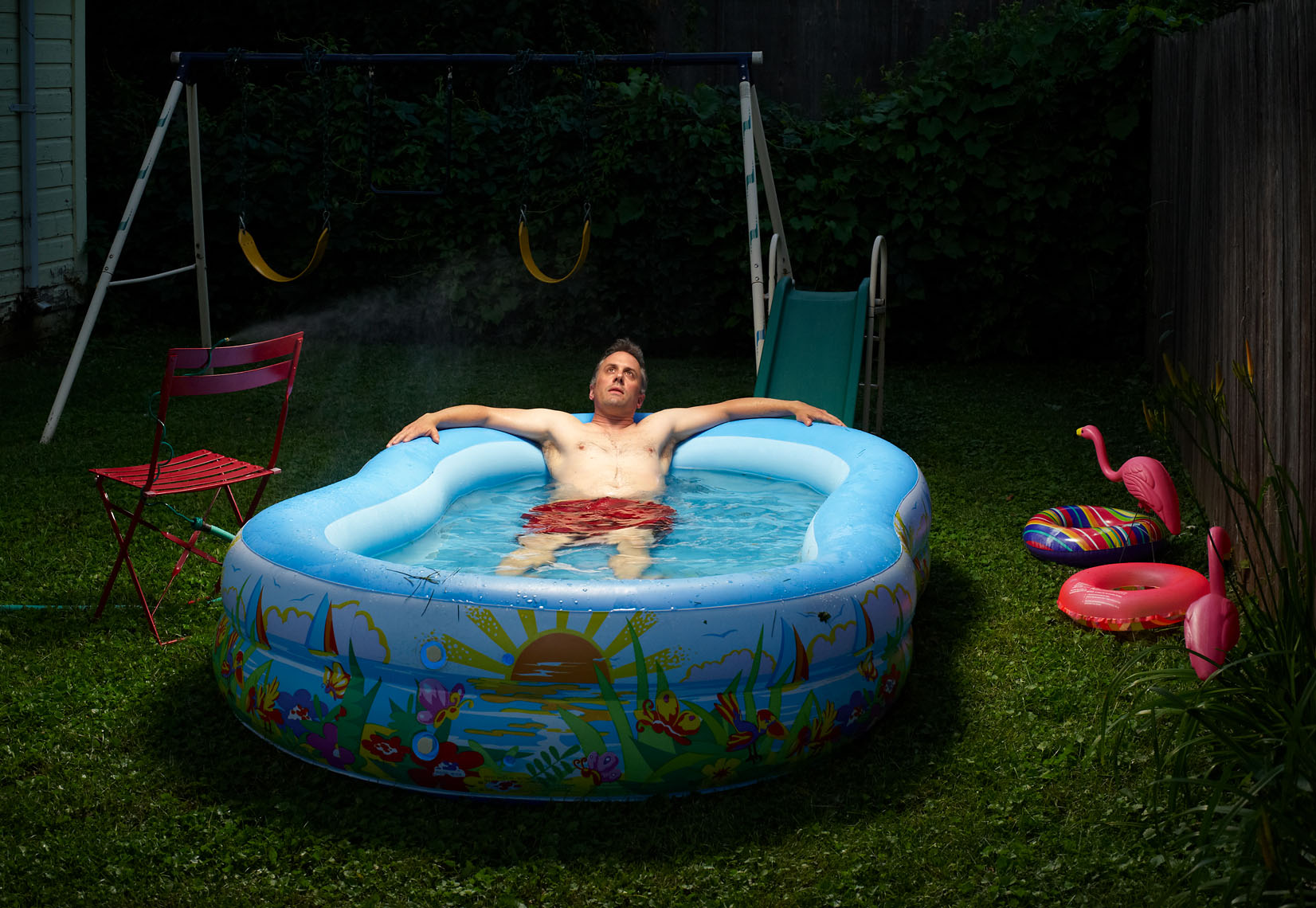 Middle aged man soaks in kiddie pool lifestyle